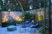 Small courtyard garden at dusk, contemporary chairs and table by Cane Line on sawn grey Yorkstone patio, lit galvanised steel screen by Steel Sculptures, Chamaerops humilis