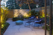 Small courtyard garden at dusk, contemporary chairs and table by Cane Line on sawn grey Yorkstone stone patio, lit galvanised steel screen by Steel Sculptures, Chamaerops humilis, Phyllostachys aurea