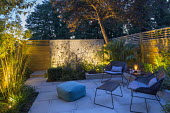 Small courtyard garden at dusk, contemporary chairs and table by Cane Line on sawn grey Yorkstone patio, lit galvanised steel screen by Steel Sculptures, Chamaerops humilis, Phyllostachys aurea