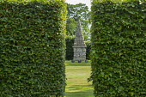 View through hornbeam hedges towards stone obelisk