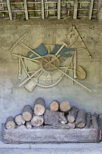 Sculpture made from old tools mounted onto wall, log store