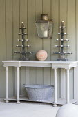 Recycled wooden candelabra and terracotta ball on table, wall-mounted lantern, zinc tub