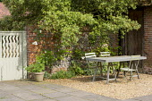 Table and chairs on gravel terrace by brick wall