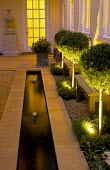 Formal stone-edged rill with fountains, urn on plinth, row of uplit standard Cupressus arizonica, wooden benches