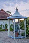 Agave americana in large terracotta pot under formal sentry post, gravel driveway, spiral box topiary