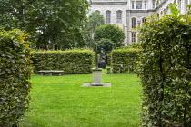 Hornbeam hedges around lawn, sculptures on plinths, stone bench