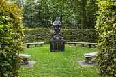 Sculpture on plinth in hornbeam hedge enclosure, stone benches
