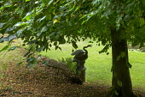 Stone statue of swan under tree