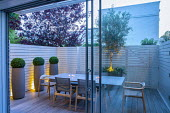 View from inside house through sliding glass doors to table and chairs in small courtyard garden outside, white painted wooden fence, up-lit olive tree and box balls in containers