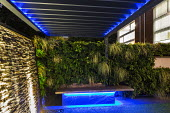 Contemporary adjustable pergola, lit stone wall water cascade, built-in benches with underlighting, living green wall, Carex oshimensis 'Evergold'