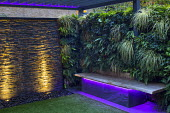 Lit stone wall water cascade, astroturf lawn, built-in bench with underlighting, living green wall, Carex oshimensis 'Evergold'
