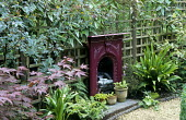 Reclaimed cast-iron fireplace against wooden trellis, Clematis armandii, Asplenium scolopendrium
