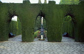 Clipped arches in yew hedges, formal canal, stone paving