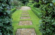 Stepping stone path of brick squares set into lawn, box-edged borders