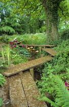Timber boardwalk path over bog garden, Primula pulverulenta, iris, fish ornaments on stakes