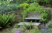 Dry-stone wall, rustic bench and stone table, thyme, lavender, honeysuckle, roses