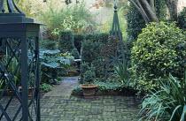 Green painted obelisks in courtyard garden, brick paving, acanthus