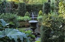 Fountain in classical urn in sunken courtyard garden