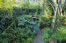 Fountain in classical urn in sunken courtyard garden, green painted obelisks, acanthus