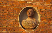Terracotta bust in niche in brick wall of orangery