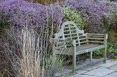 Wooden Lutyens bench on stone paving, heather in raised bed