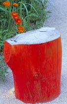 Orange painted log stool