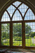 View from inside through Gothic window to formal topiary garden outside