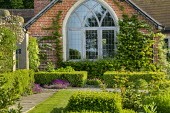 Gothic window in house, low clipped box hedges, stone path