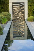 Formal canal edged with grey Yorkstone, granite water wall, reflections, Pinus sylvestris 'Watereri'