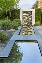 Bridge over formal canal edged with grey Yorkstone, granite water wall, basalt granite gravel, Pinus sylvestris 'Watereri'