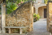 View into mediterranean courtyard, stone bench