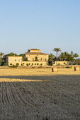 View across field of harvested hay to mediterranean villa