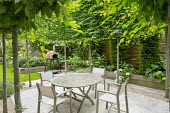 Table and chairs on travertine patio edged with gravel within pleached hornbeam enclosure, yew columns and Hydrangea arborescens 'Annabelle' in timber raised bed, outdoor oven