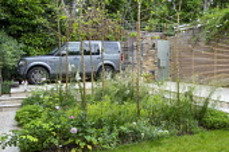 Path leading to car on front garden driveway, Malus x robusta 'Red Sentinel' grove, Alchemilla mollis, Deschampsia cespitosa 'Goldschleier', allium seedheads