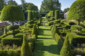 Overview across formal parterre, yew topiary, armillary sphere