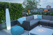 Contemporary roof terrace at dusk, outdoor sofas with cushions, uplit olive tree in raised bed, lavender, Verbena bonariensis, lantern