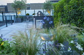 Outdoor kitchen on roof terrace, stools by breakfast bar, decking, Stipa tenuissima and lavender in raised bed, glass screen, uplit olive trees, agapanthus in container