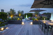 Roof terrace at night, uplit olive trees, raised beds, decking, umbrellas over table and chairs and outdoors sofas, lanterns