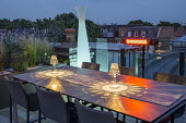 Lanterns on table on roof terrace at night, glass screens, heater