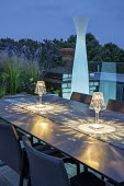Lanterns on table on roof terrace at night, glass screen