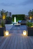 Roof terrace at night, uplit olive trees, raised beds with lavender and Stipa tenuissima, outdoor rug on decking, outdoor sofas, lanterns