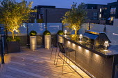 Outdoor kitchen, grill and breakfast bar with stools on roof terrace at night, yew domes in tall containers, glass screens, uplit olive trees, decking