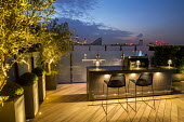 Outdoor kitchen, grill and breakfast bar with stools on roof terrace at night, yew domes in tall containers, glass screens, decking