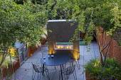 Contemporary roof terrace, multi-stemmed Crataegus monogyna in Cor-Ten steel planters underplanted with Geranium 'Rozanne' and Hakonechloa macra, table and chairs, outdoor fridge and fireplace