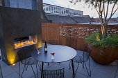 Table and chairs on roof terrace, Cor-Ten steel screen, built-in fireplace, multi-stemmed Crataegus monogyna in large Cor-Ten steel planter underplanted with Geranium 'Rozanne' and Hakonechloa macra