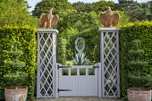Wooden gate, eagle ornaments on trellis piers, hornbeam hedge, box topiary in terracotta pots, view to agave