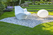 Contemporary chair and light in gravel terrace in sloping lawn