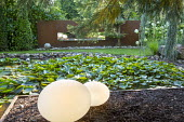 Contemporary lights by water lily pondk, Cor-ten steel screen