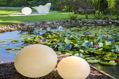Contemporary lights by water lily pond