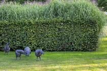 Hornbeam hedge, bird sculptures by Jef Claerhout on lawn, Miscanthus sinensis 'Zebrinus'